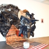 Abigail Deville<br> <em>New York at Dawn</em>, 2010 <br> Tyvek, enamel and latex paint, dirt, American flags, graphite, lamp shade, synthetic hair, polyurethane varnish, chicken wire, plastic sheeting, plaster, garbage bags, pâpier-maché, fake eyelaches, duct tape, wood chips, wire, canvas, cigarette butt, acrylic yarn, metal, salt dough, and hardware <br> 8.5 x 9.5 x 8 feet